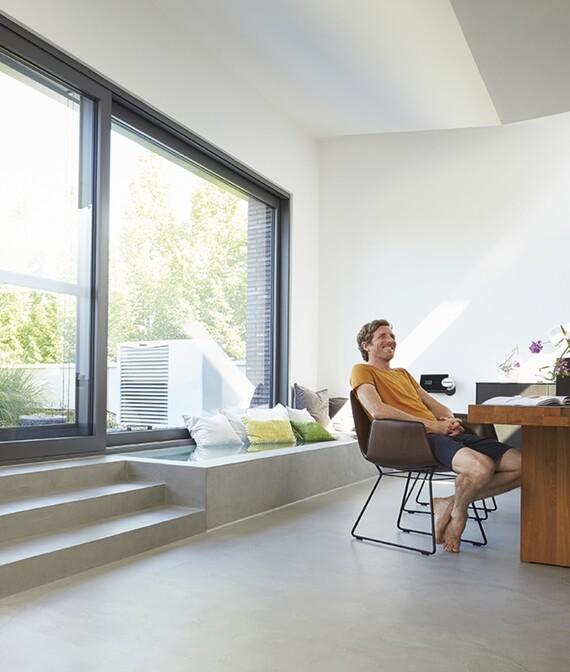 Usuario en vivienda con uniTOWER en el interior y aroTHERM en el exterior