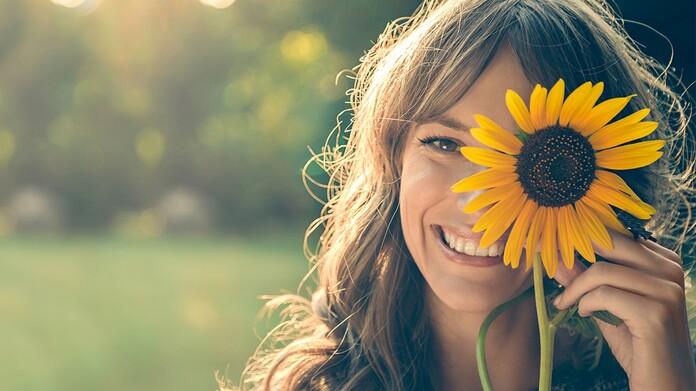 Mujer sonriendo con un girasol
