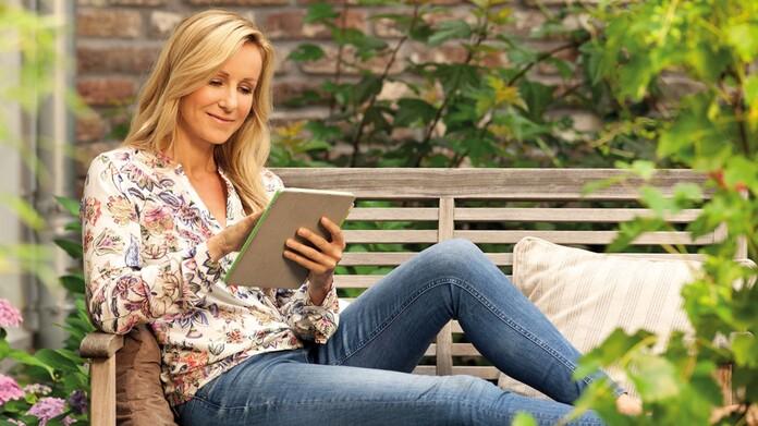 Mujer sentada en leyendo una tablet