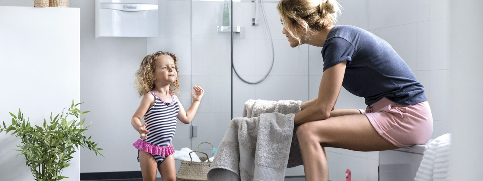 Madre con una niña en el baño. Al fondo puede verse una caldera de condensación.