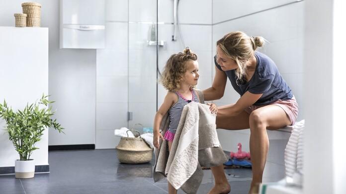 Madre secando el pelo a su hija en el baño, de fondo se puede ver una caldera de condensación.