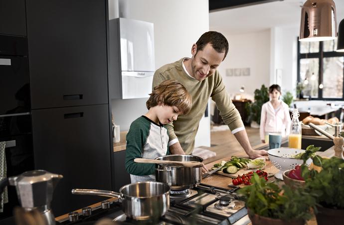 Familia cocinando con caldera de fondo