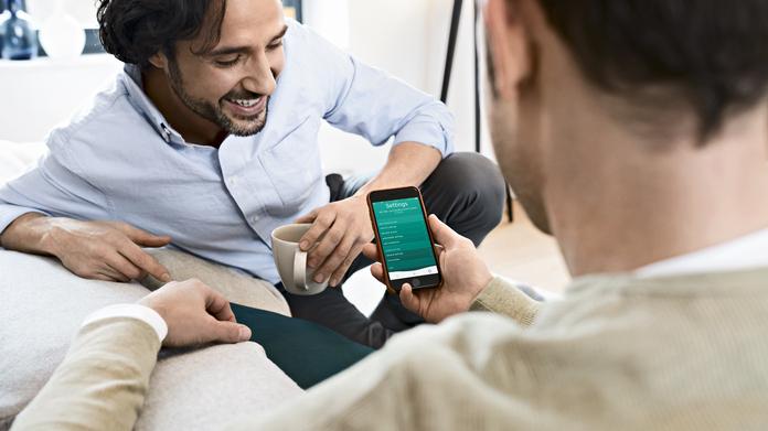 Dos hombres en un sofáutilizando la app de Vaillant