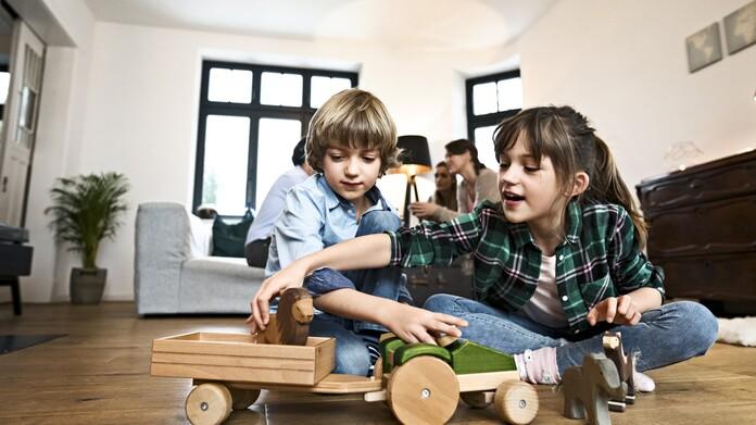 Niños jugando en el suelo de una sala de estar